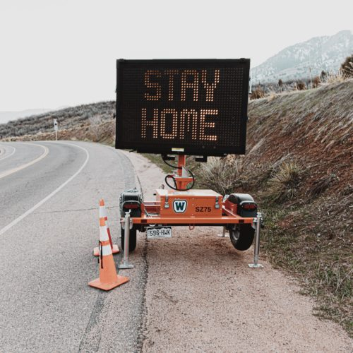 A digital sign says Stay Home on the side of an empty road. Road trip covid-19.